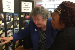 Sr Angela Hallahan discusses the picture display with a guest